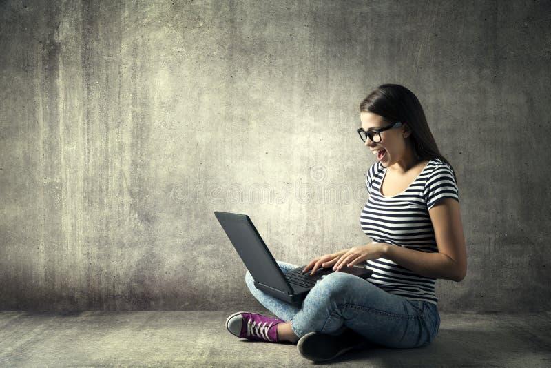 Kvinna som använder bärbara datorn, lycklig flicka i exponeringsglas på anteckningsbokdatoren arkivfoto