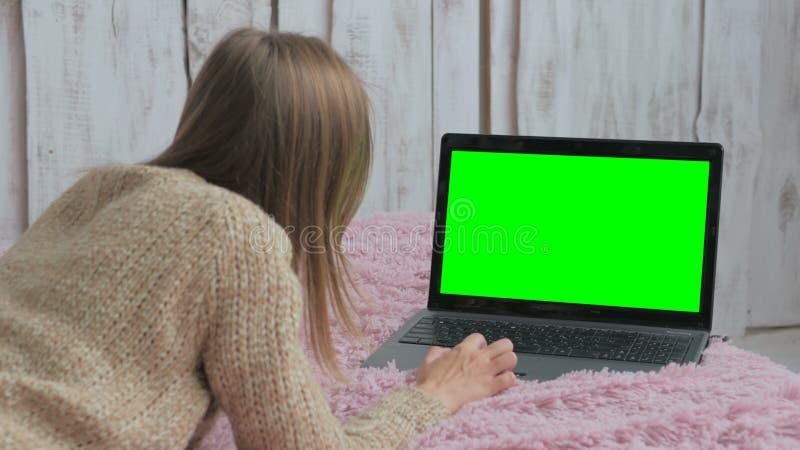 Kvinna som använder bärbara datorn med den gröna skärmen royaltyfria bilder