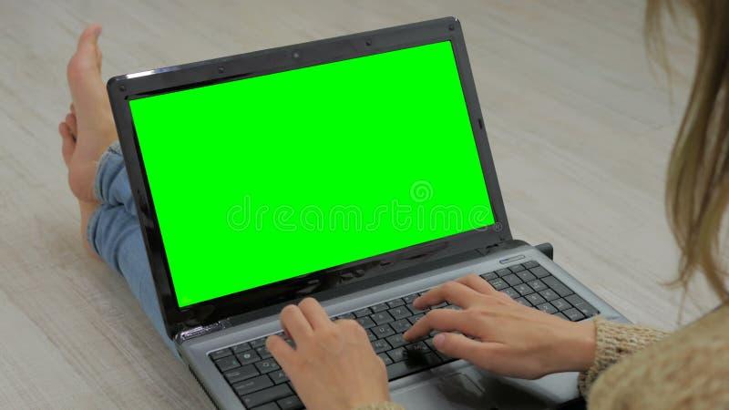 Kvinna som använder bärbara datorn med den gröna skärmen royaltyfria foton