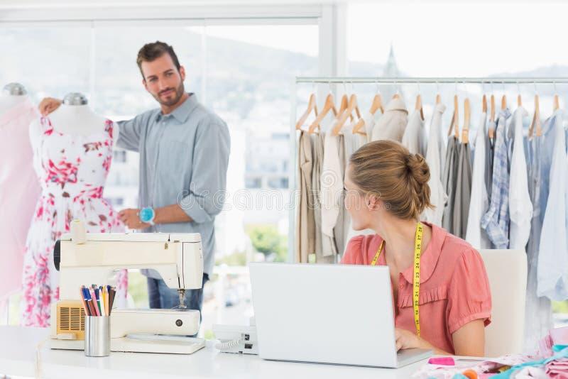Kvinna som använder bärbara datorn med modeformgivaren som arbetar på studion royaltyfri foto