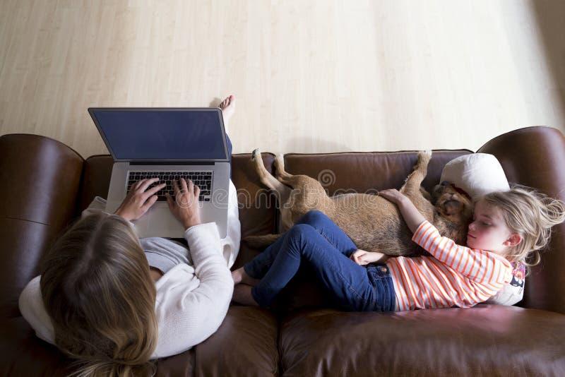 Kvinna som använder bärbara datorn, medan dottern och hunden sover arkivfoton