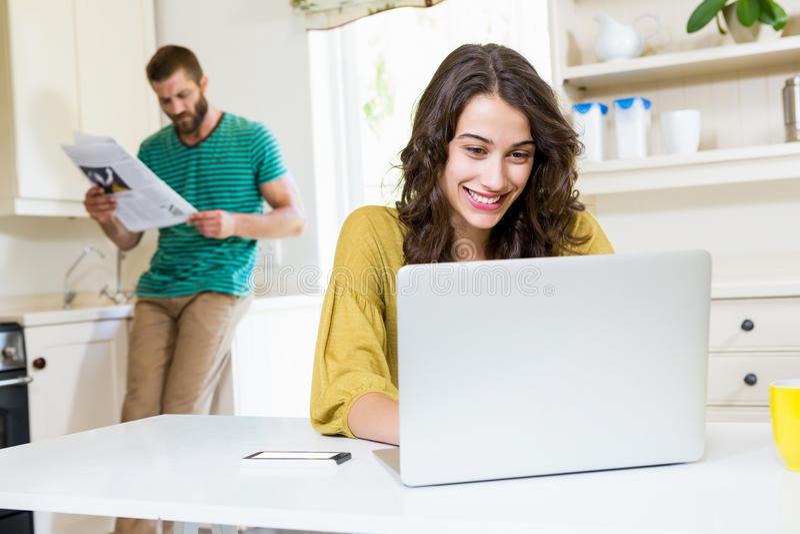 Kvinna som använder bärbara datorn medan läs- tidning för man i bakgrund royaltyfria bilder