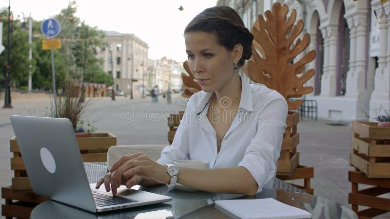 Kvinna som använder bärbara datorn och fri wifi på det utomhus- kafét royaltyfri foto