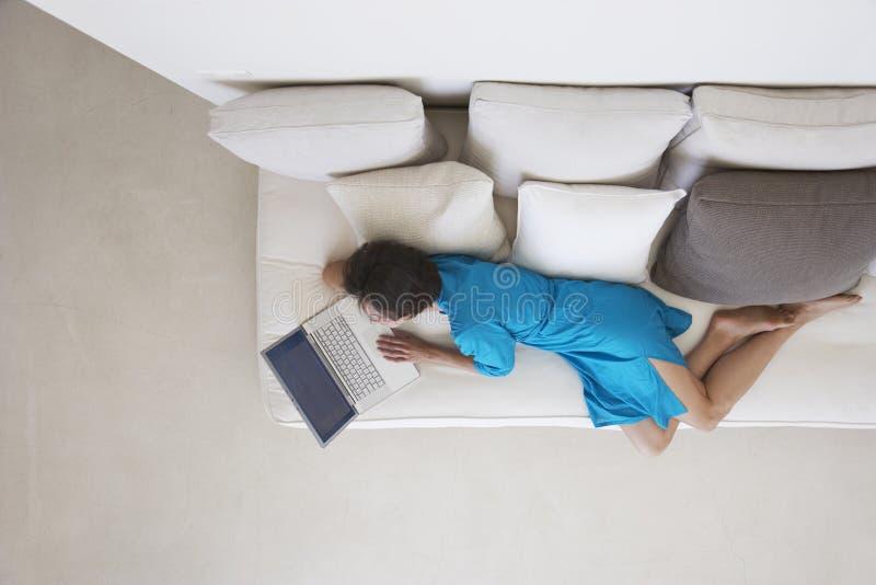 Kvinna som använder bärbara datorn på soffan i vardagsrum arkivfoton
