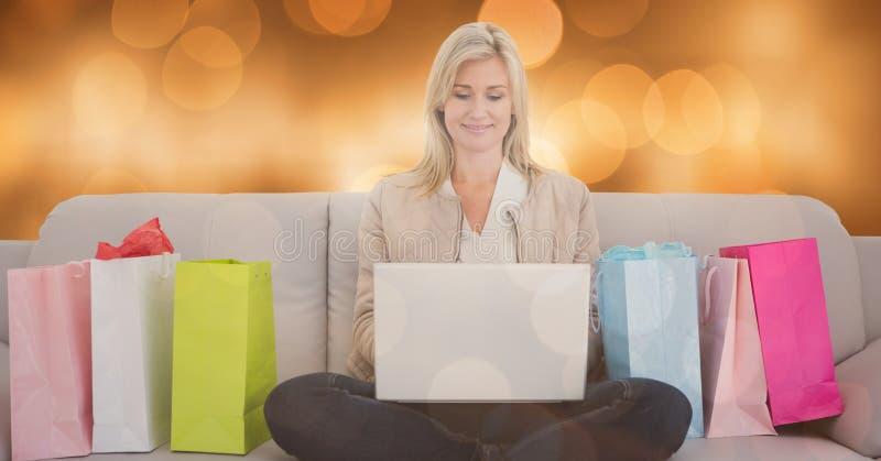 Kvinna som använder bärbara datorn vid shoppingpåsar på soffan över bokeh arkivfoto