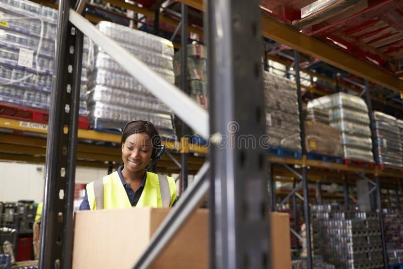 Kvinna som använder barcodeavläsaren i lager, head och skuldror arkivfoto