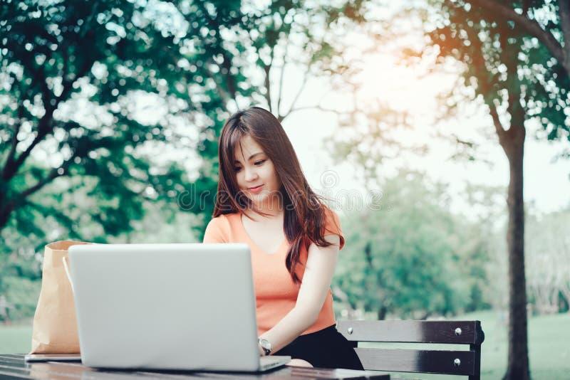 Kvinna som använder begrepp för anteckningsbok för bärbar datordator utomhus- arkivfoton
