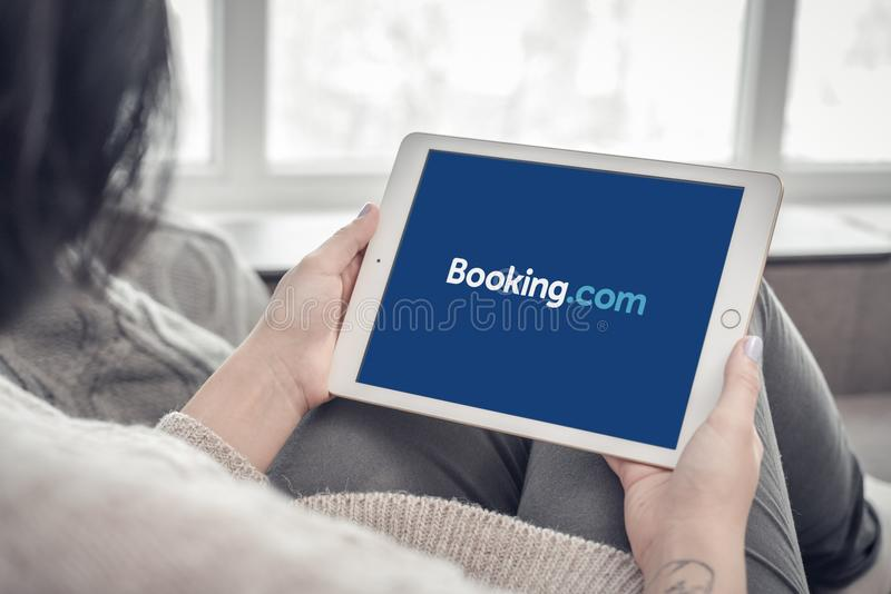 Kvinna som använder bokning com app på splitterny en pro-Apple iPad royaltyfri foto