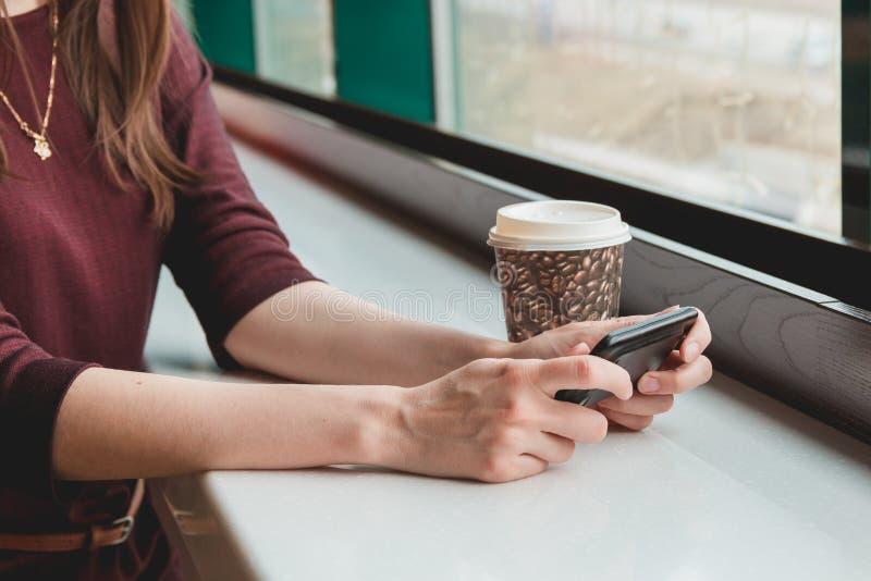 Kvinna som använder celltelefonen, medan vila i coffee shop royaltyfri bild