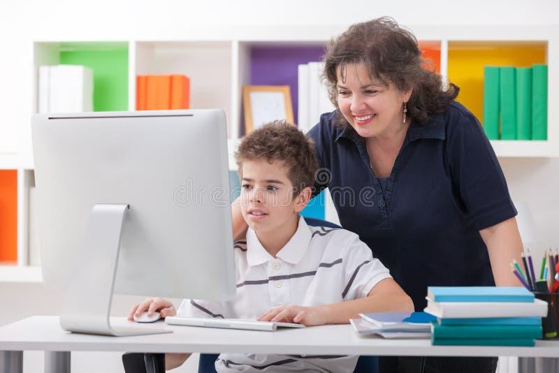 Kvinna som använder datoren med sonen royaltyfri bild