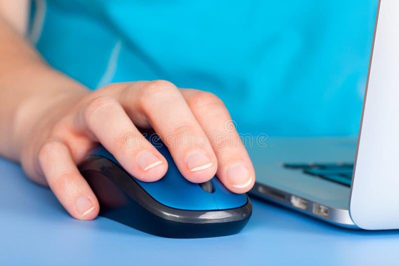 Kvinna som använder datormusen på bärbara datorn arkivfoton