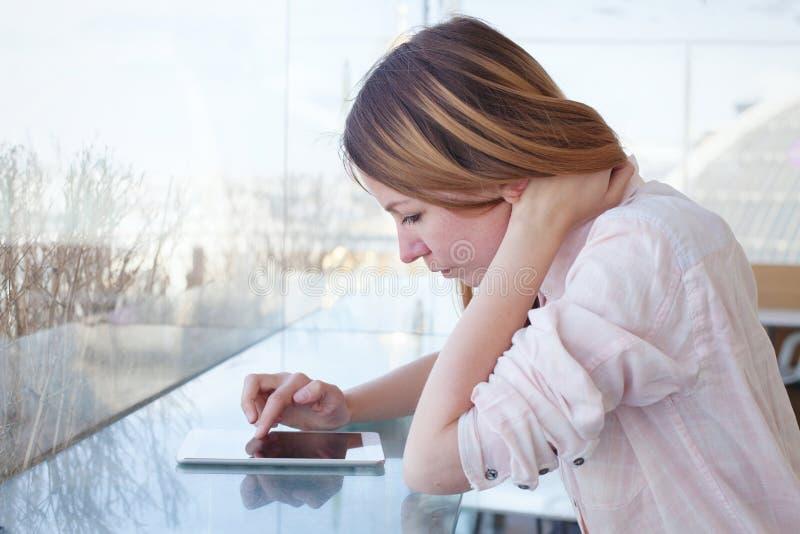 Kvinna som använder den digitala minnestavlagrejen i den moderna inre som kontrollerar emailen royaltyfri bild