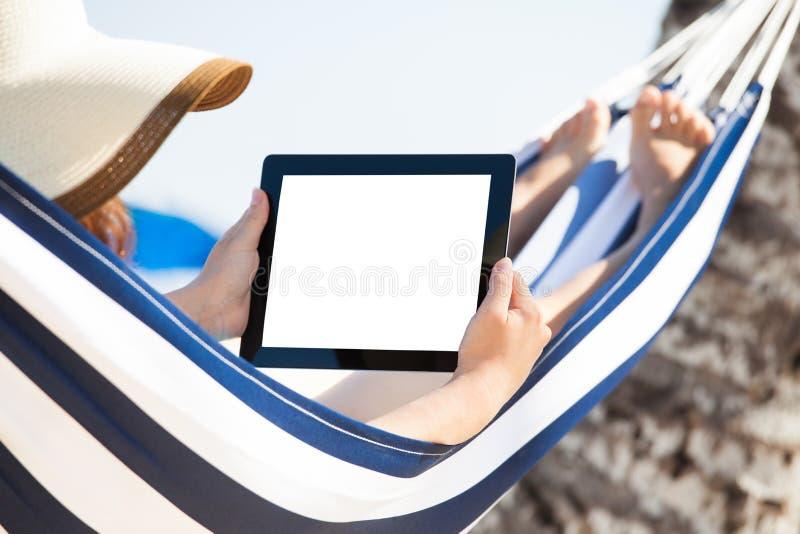 Kvinna som använder den digitala minnestavlan i hängmatta royaltyfri bild