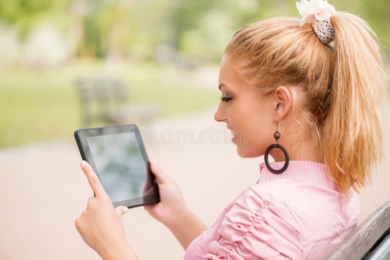 Kvinna som använder den digitala minnestavlan i parkera fotografering för bildbyråer