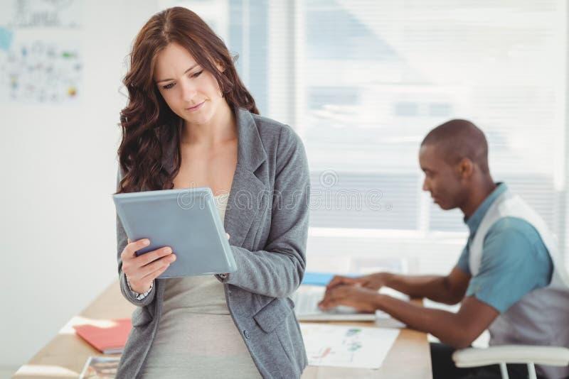 Kvinna som använder den digitala minnestavlan med mannen som arbetar på skrivbordet royaltyfri foto