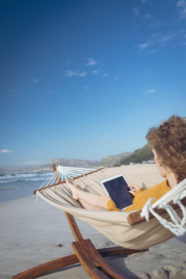 Kvinna som använder den digitala minnestavlan, medan ligga på hängmattan royaltyfri foto