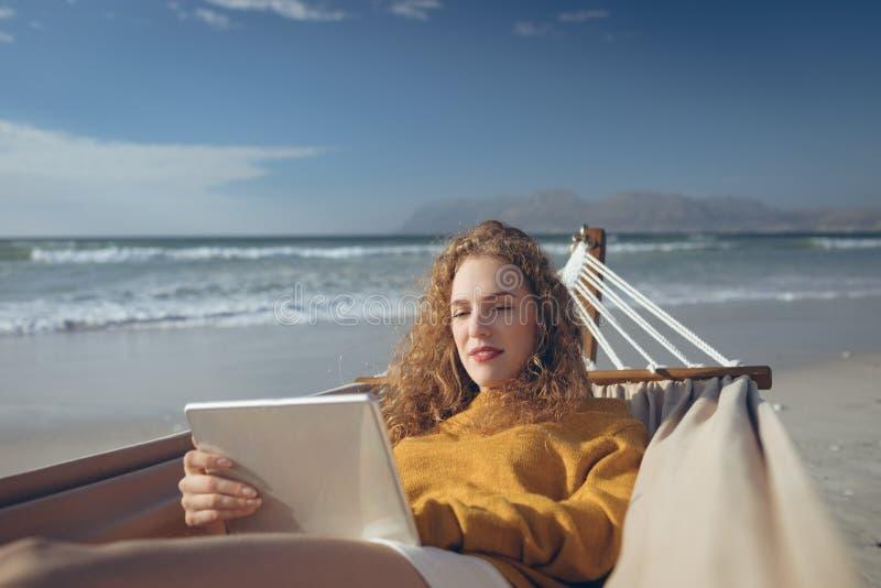 Kvinna som använder den digitala minnestavlan, medan ligga på hängmattan på stranden royaltyfria foton