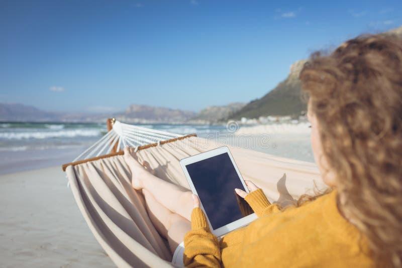 Kvinna som använder den digitala minnestavlan, medan luta på hängmattan arkivfoton