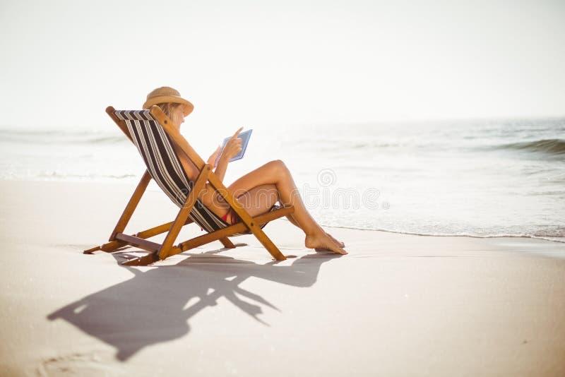 Kvinna som använder den digitala minnestavlan på stranden fotografering för bildbyråer