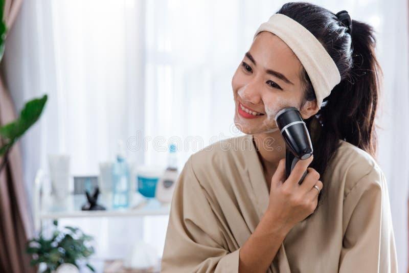 Kvinna som använder den elektriska ansikts- rengöringsmedelmaskinen royaltyfria foton
