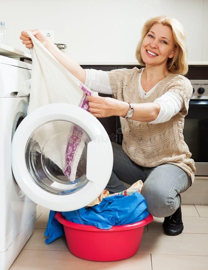 Kvinna som använder den hemmastadda tvätterit för tvagningmaskin arkivfoto