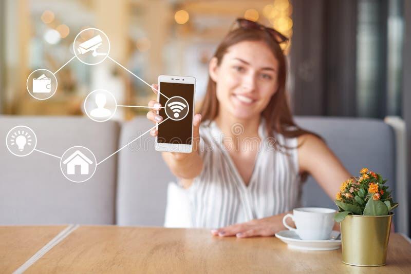 Kvinna som använder den moderna mobila smarta telefonen som förbinder till wifiautomationapps Avlägsen faktisk kontroll hemma arkivfoto