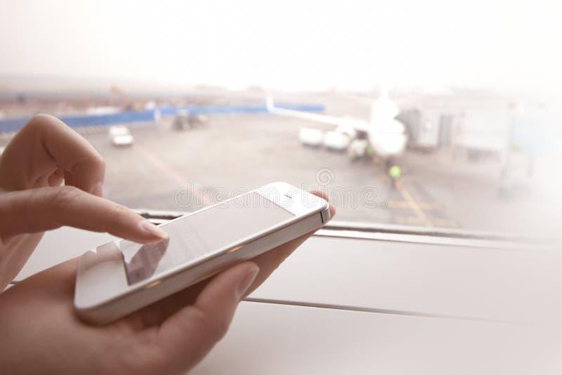 Kvinna som använder den smarta telefonen vid fönstret på aiport royaltyfri bild