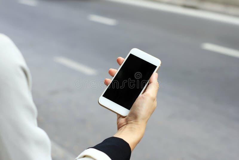Kvinna som använder den smarta telefonen vid gatan, genom att använda tjänste- applikation för taxi arkivfoto