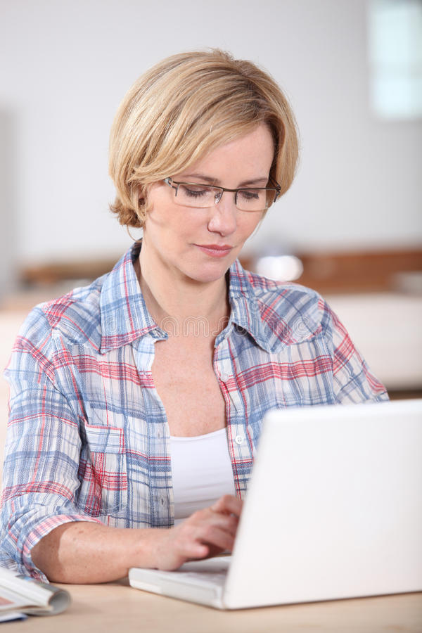 Kvinna som använder en bärbar dator c royaltyfri bild