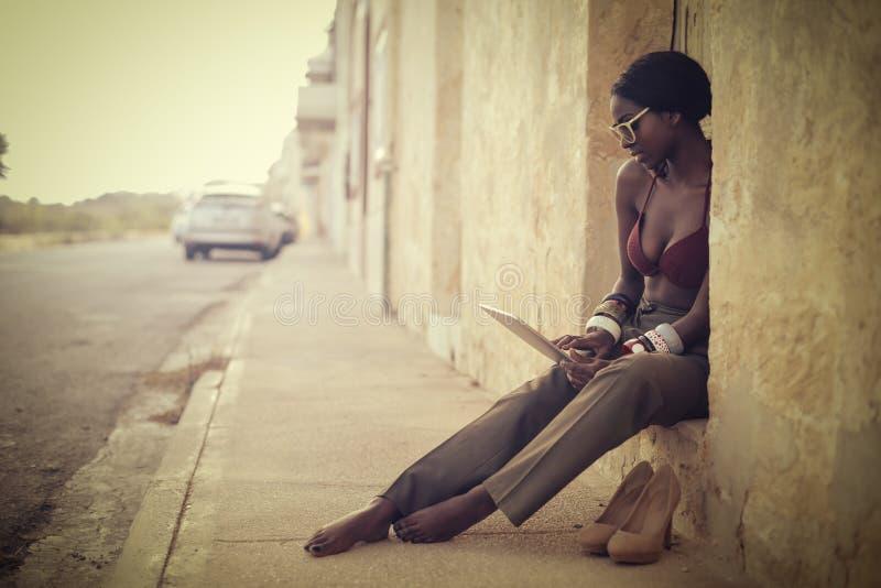 Kvinna som använder en bärbar dator på gatan royaltyfri fotografi