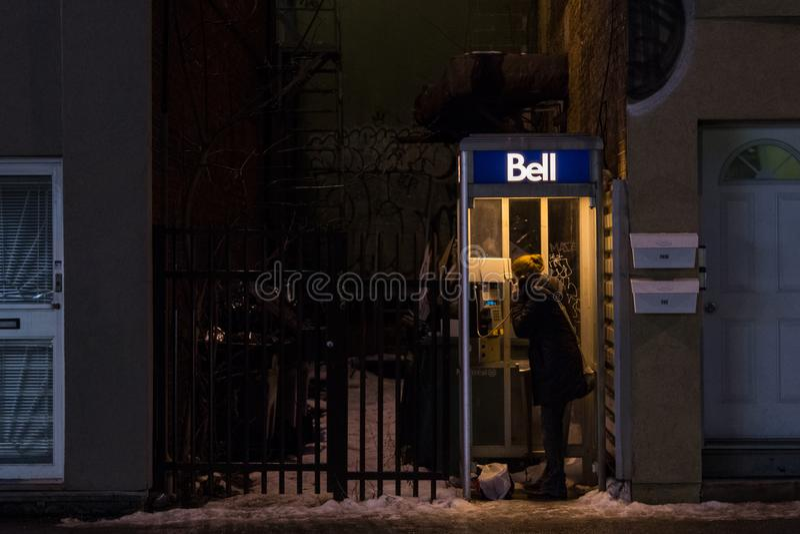 Kvinna som använder en Bell Canada Payphone i Montreal i aftonen under tung snö royaltyfri foto
