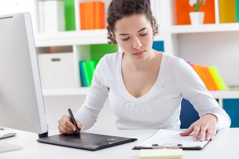 Kvinna som använder en grafisk minnestavla och en penna royaltyfria bilder