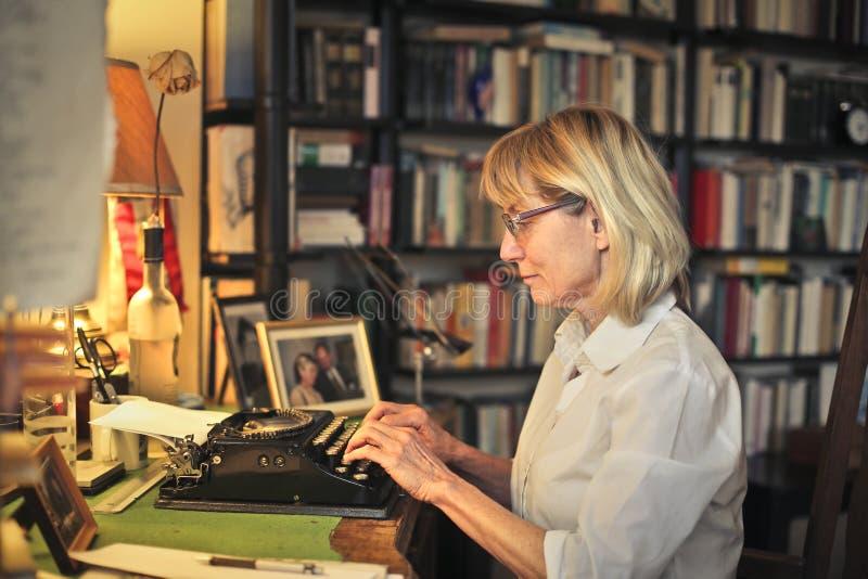 Kvinna som använder en maskinskrivningmaskin royaltyfria bilder