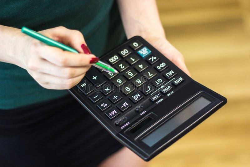 Kvinna som använder en räknemaskin med en penna i hennes hand, beräknande hemmastatt kontor för finansiell kostnad fotografering för bildbyråer