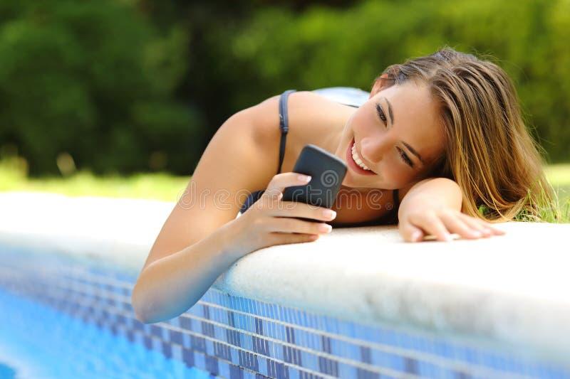 Kvinna som använder en smart telefon i en poolside i sommar royaltyfri foto