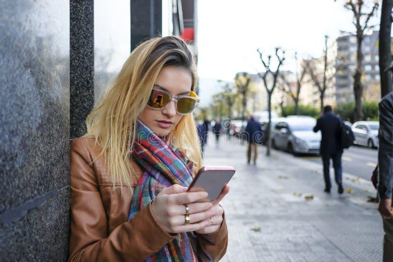 Kvinna som använder en smart telefon i gatan royaltyfria foton