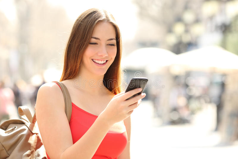 Kvinna som använder en smart telefon i gatan i sommar royaltyfria bilder
