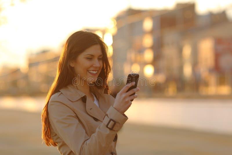 Kvinna som använder en smart telefon på solnedgången i gatan arkivfoton