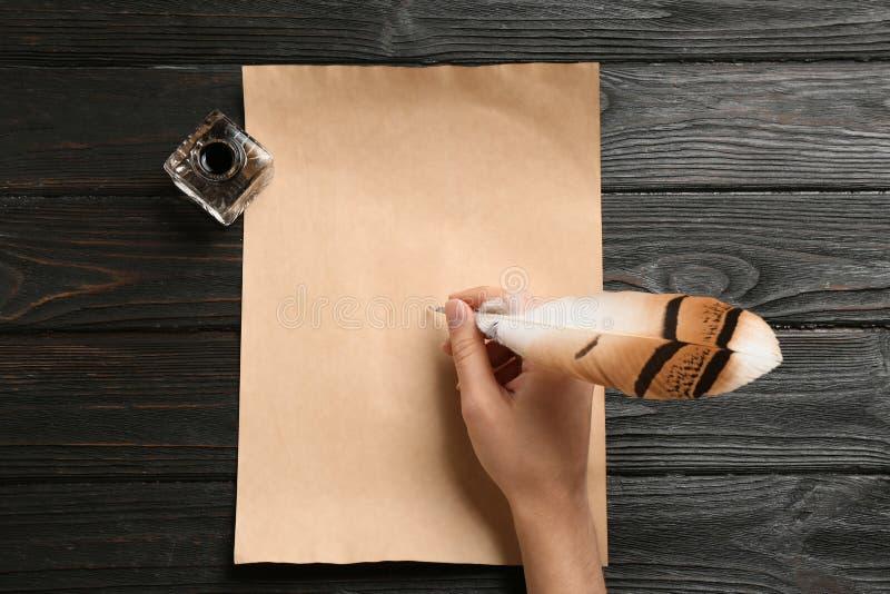 Kvinna som använder fjäderpennan för att skriva med färgpulver på pergament på trätabellen, bästa sikt royaltyfria foton