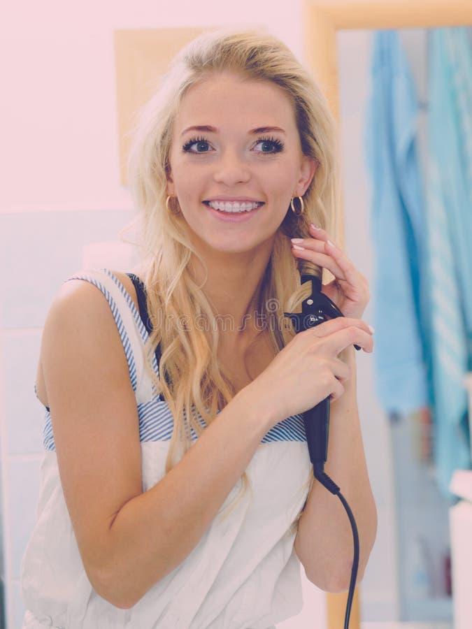 Kvinna som använder hårstraighteneren royaltyfri foto
