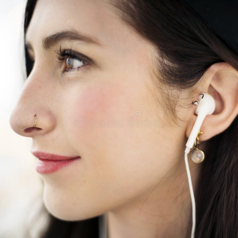 Kvinna som använder hörlurar som lyssnar till musik arkivfoton