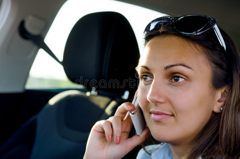 Kvinna som använder henne som är mobil i en bil royaltyfria bilder