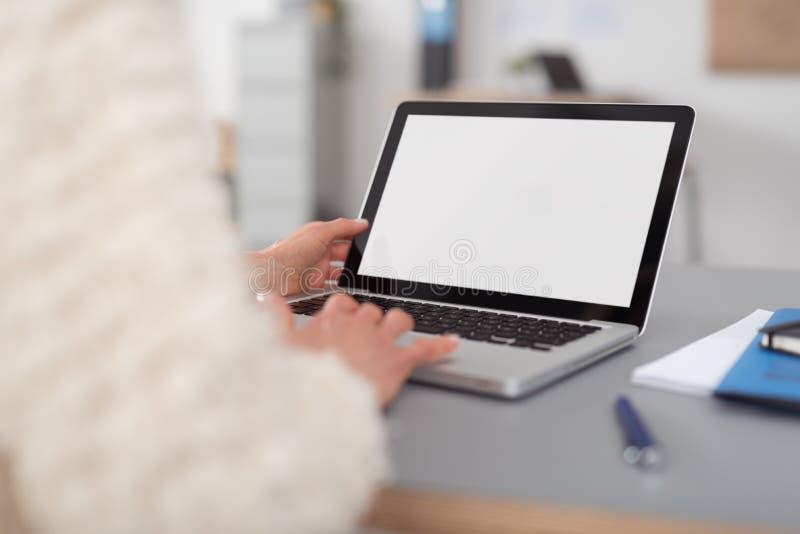 Kvinna som använder hennes bärbar dator med den tomma vita skärmen fotografering för bildbyråer