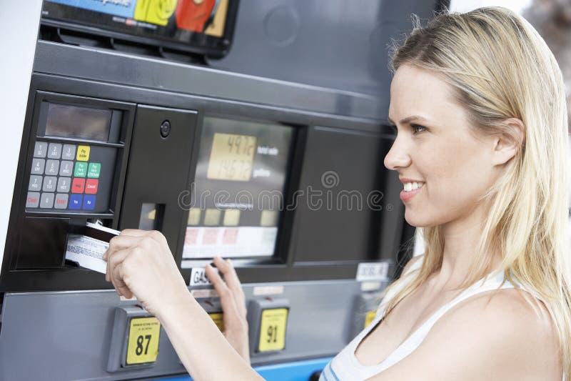Kvinna som använder hennes debiteringkort för att betala för bensin royaltyfria bilder