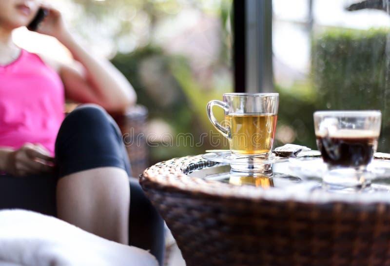 Kvinna som in använder hennes mobiltelefon med kopp te och kaffe på arkivfoton