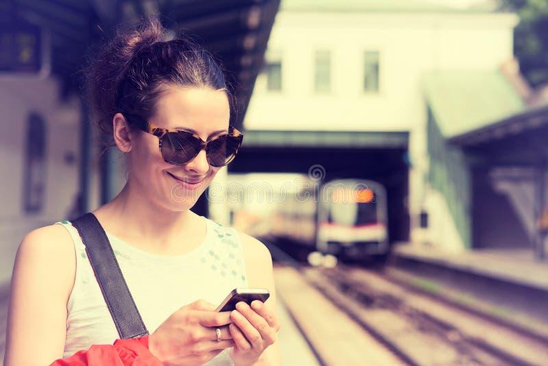 Kvinna som använder hennes mobiltelefon på gångtunnelplattformen som kontrollerar drevschema royaltyfri foto