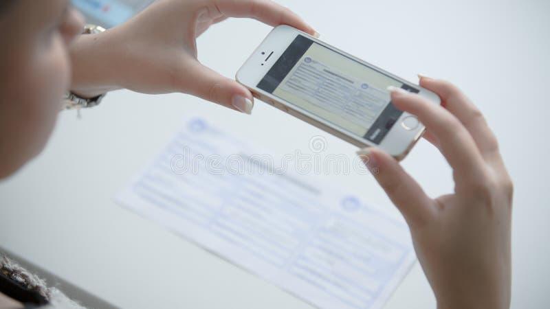 Kvinna som använder hennes telefon för att ta bilden av kvittot eller räkningen Direktanslutet betala räkningar från komfort av h royaltyfri fotografi