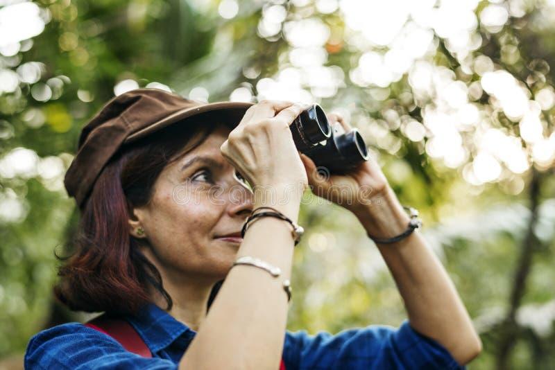 Kvinna som använder kikare, medan trekking royaltyfria foton