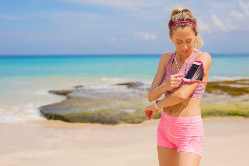 Kvinna som använder kondition spårande app på smartphonen royaltyfri bild