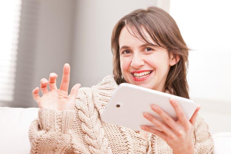 Kvinna som använder lyckat hennes minnestavla och le royaltyfri bild